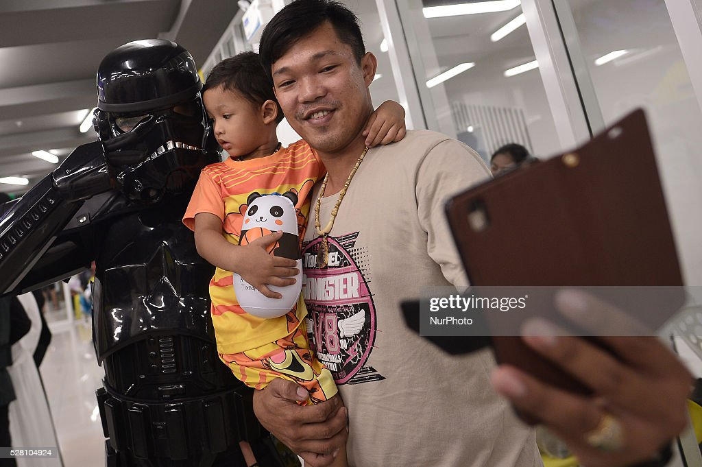 A father and son take a selfie with a man dressed as the character Dark Trooper from a famous movie Star Wars during the Star Wars day in Bangkok, Thailand on May 4, 2016.