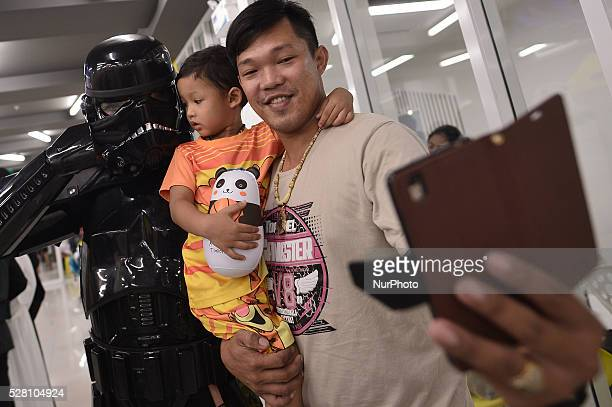 A father and son take a selfie with a man dressed as the character Dark Trooper from a famous movie Star Wars during the Star Wars day in Bangkok...