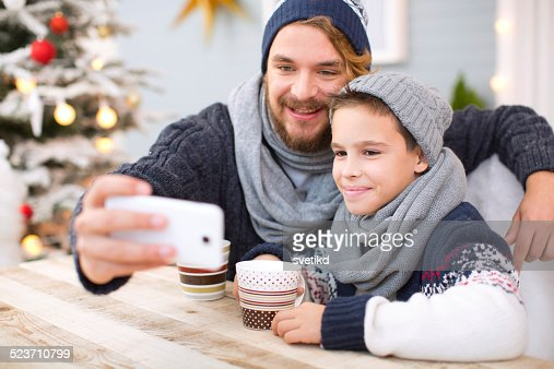 Father and son taking selfies outdoors.