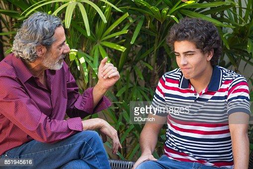 Padre e hijo hablando en un banco : Foto de stock