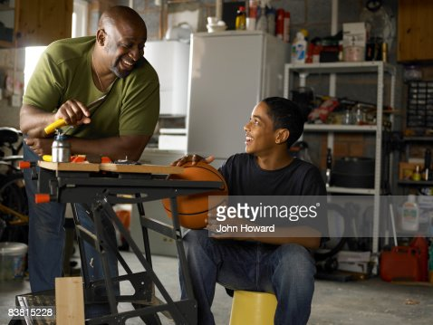 Father and Son talking over workbench in garage : Stock Photo