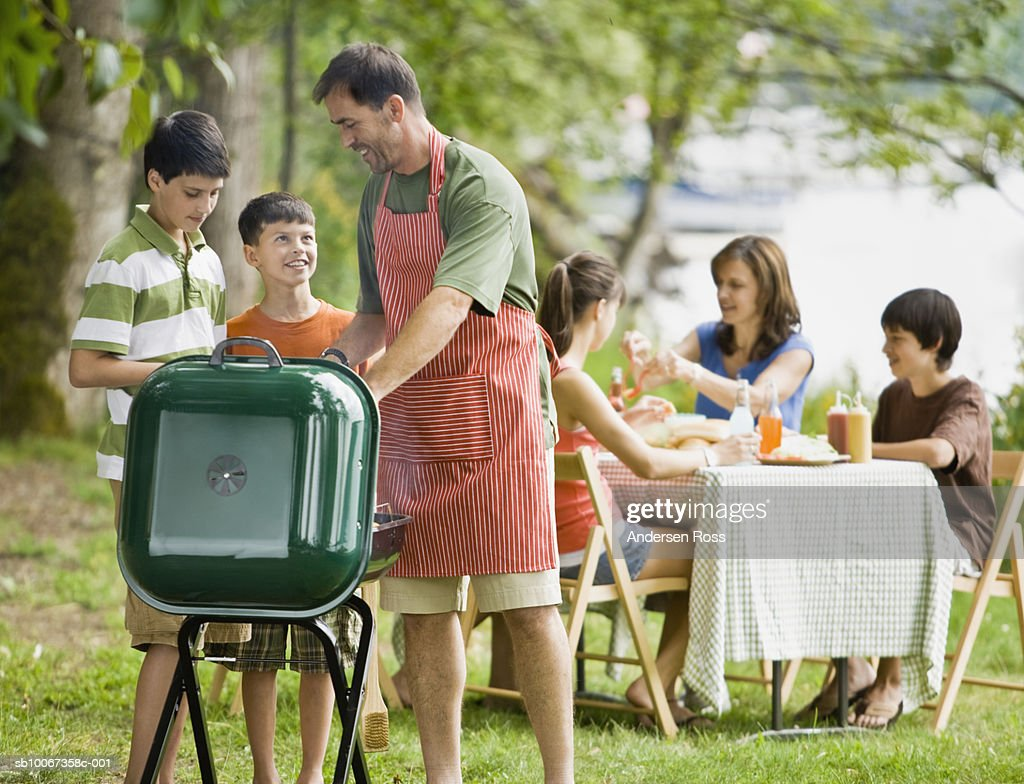 Father and son (10-14) tending barbecue, family in background : Stock Photo