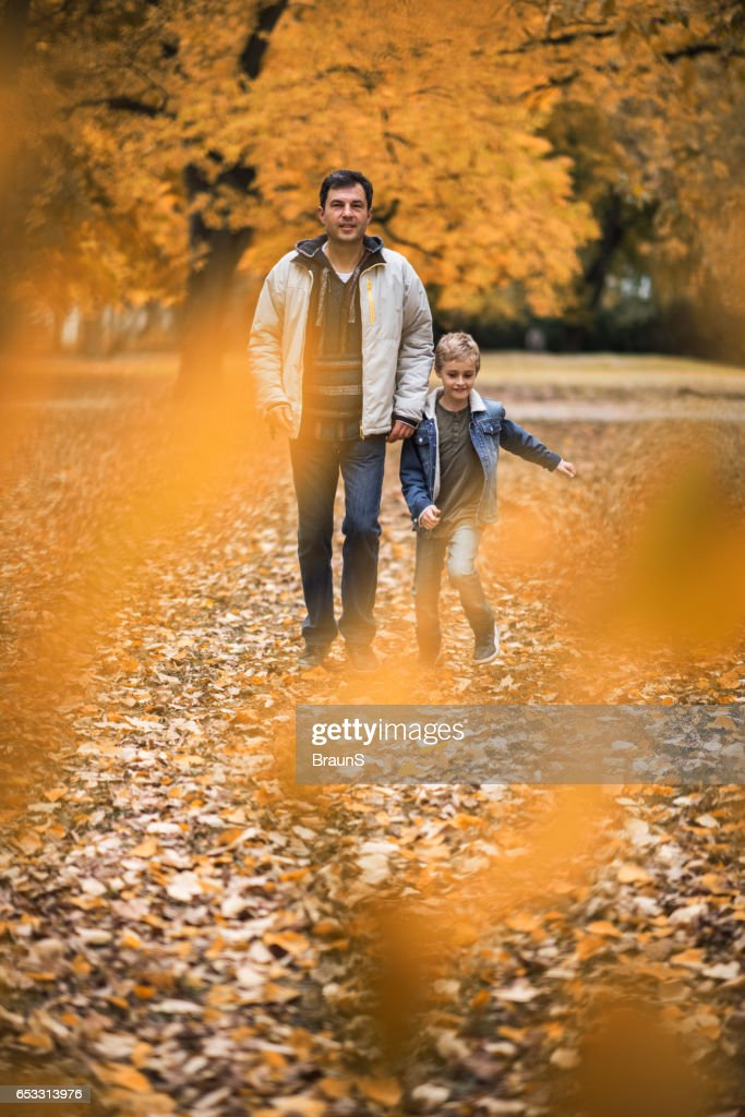 Father and son through autumn leaves in the park. : Stockfoto