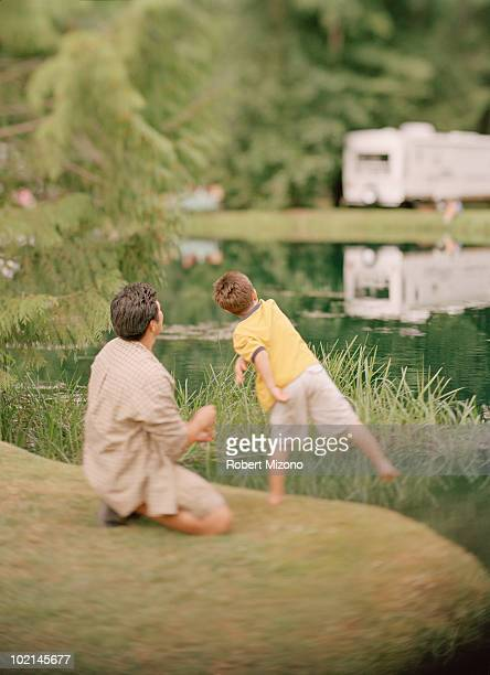 Father and son throwing rocks into pond