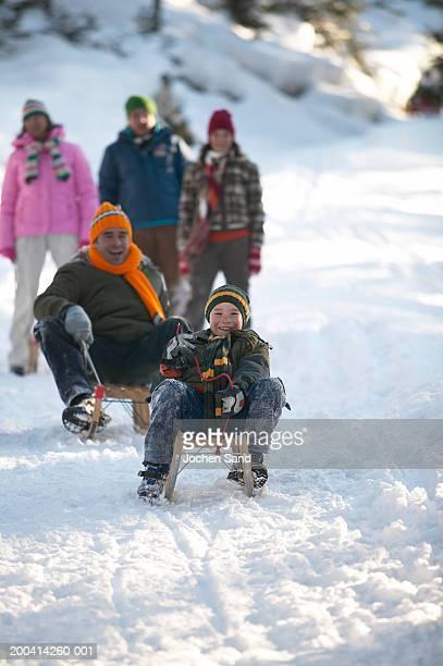 Padre e hijo (8-10) deslizarse en trineo en la nieve, su familia en el fondo