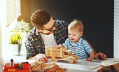 Happy family father and son toddler gather craft a car out of wood and play