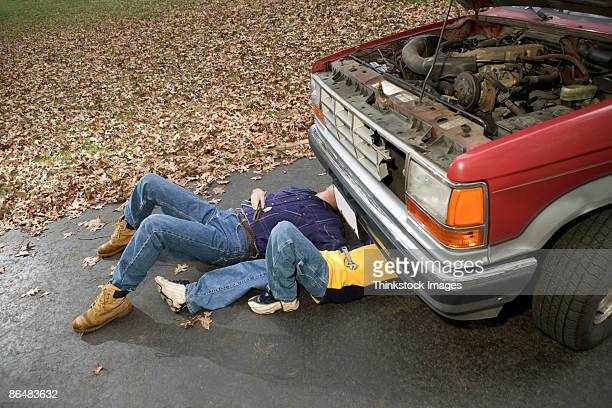 Father and son under truck