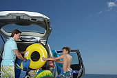 Father and son (10-12) unloading car full of beach accessories