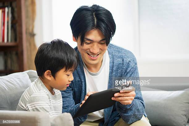 Father and son using digital tablet at home.