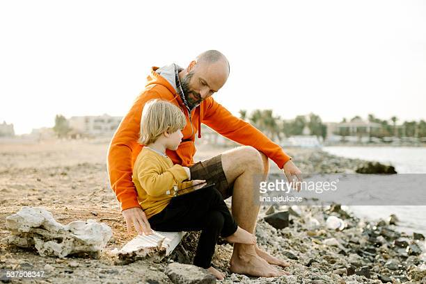 Father and son using digital tablet by the sea