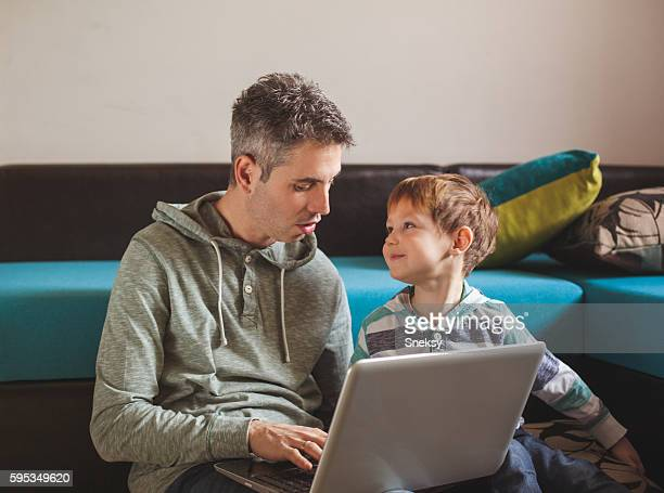 Father and son using digital tablet in family home