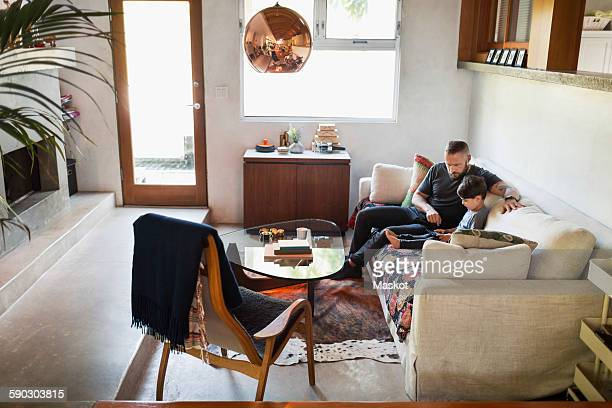 Father and son using digital tablet on sofa at home