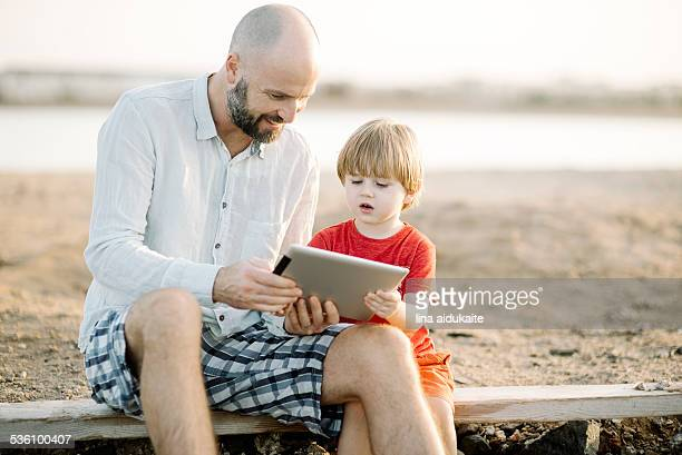 Father and son using digital tablet outside