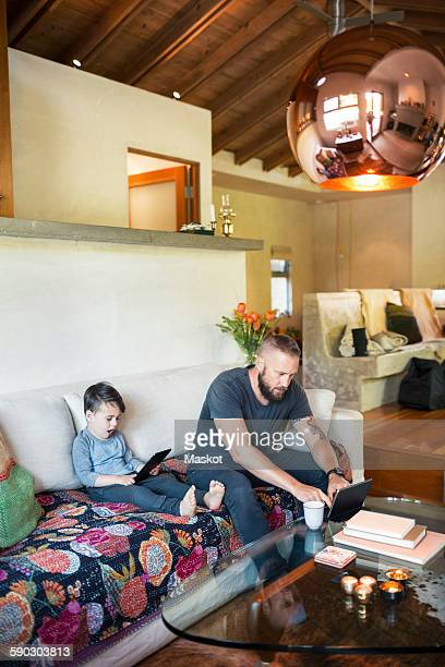 Father and son using digital tablets in living room at home