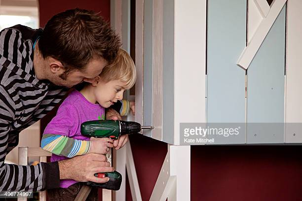 Father and son using electric screwdriver