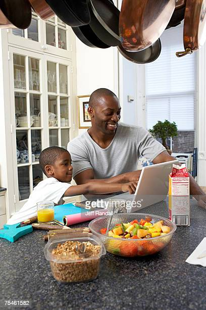 Father and son (6-7) using laptop at kitchen counter