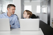 Father and son using laptops, face to face