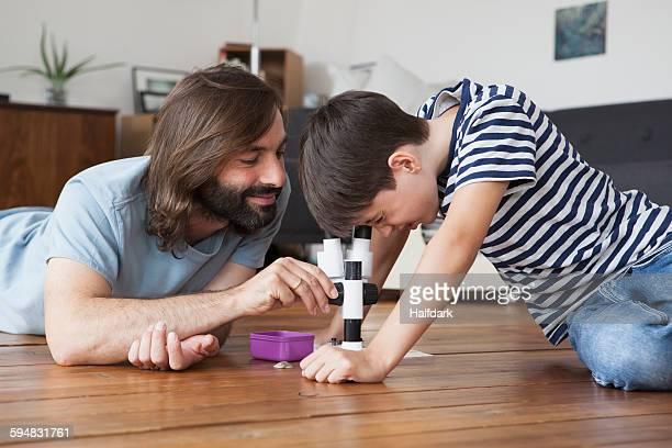 Father and son using microscope on hardwood floor