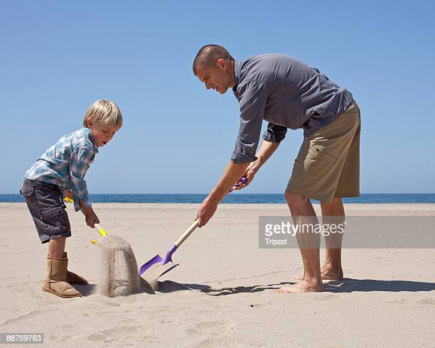 Father and son using shovels to dig hole in sand