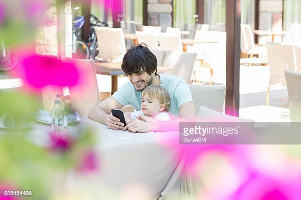 Father and son using smart phone in restaurant