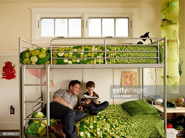 Father and son using tablet on bed
