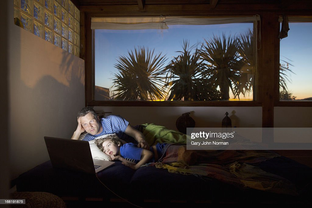 Father and son using technology at night in bed : Stock Photo