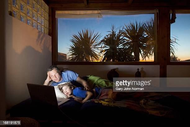 Father and son using technology at night in bed
