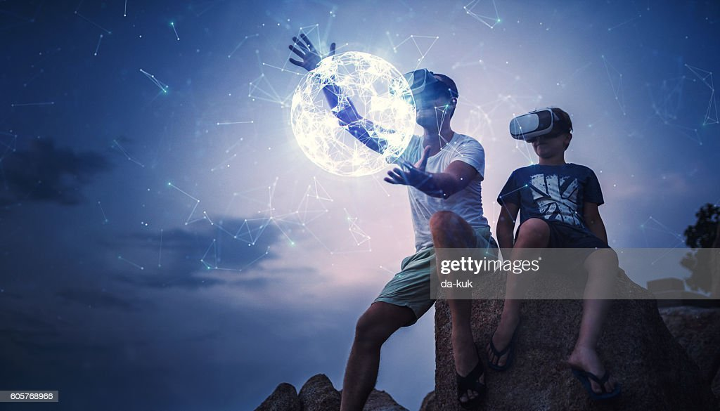 Father and son using Virtual Reality glasses sitting outside : Stock Photo