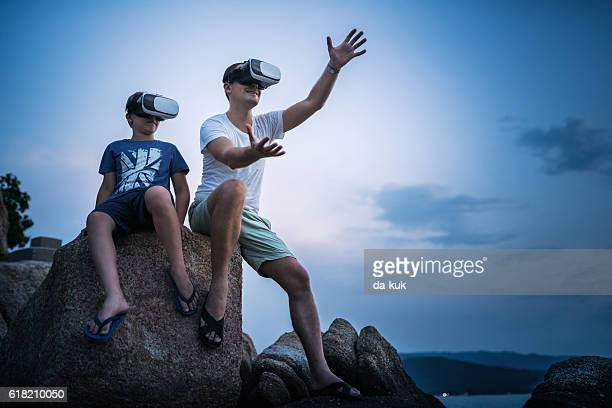 Father and son using virtual reality headset sitting outside