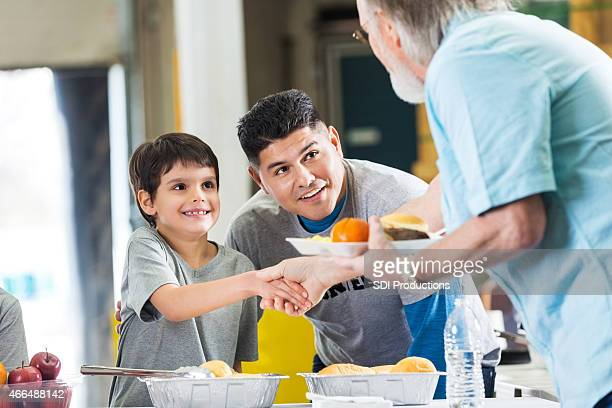 Father and son volunteering in soup kitchen together