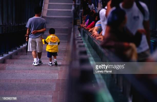 Father and son walk the escalator through Soho.
