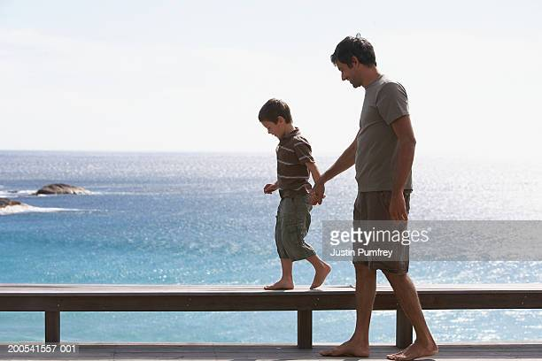 Father and son (6-8) walking along bench by sea