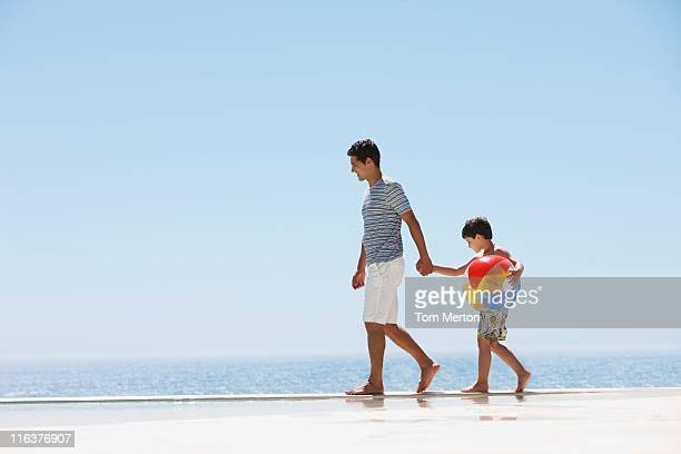 Father and son walking along infinity pool