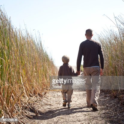 Father and son (5-7) walking down path  : Stock Photo