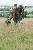 Father and son walking in rural field, Ireland