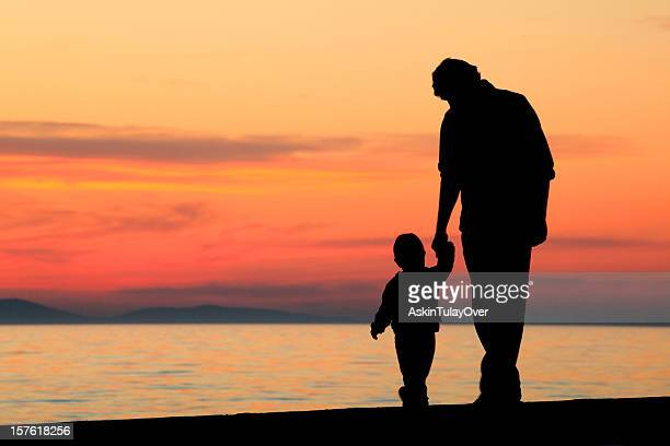 A father and son walking on a beach at sunset