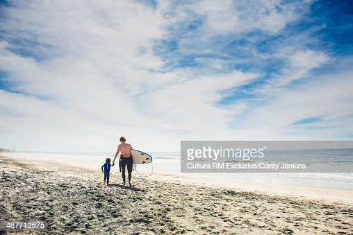 Father and son walking on beach with surfboard