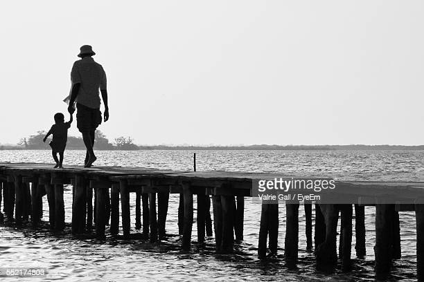 Father And Son Walking On Jetty