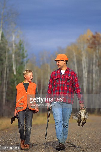 Father and son walking outdoors in hunting gear