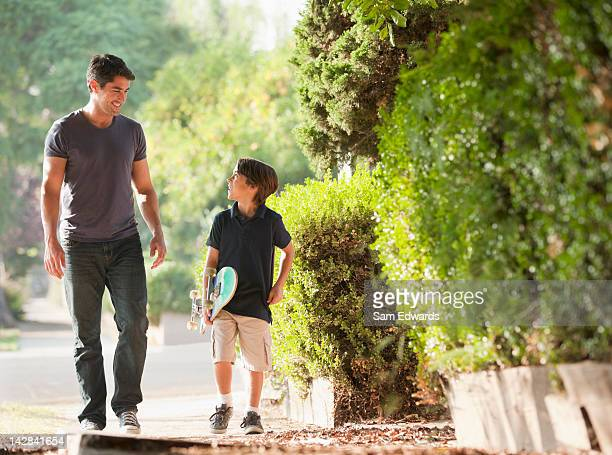 Father and son walking together on suburban street