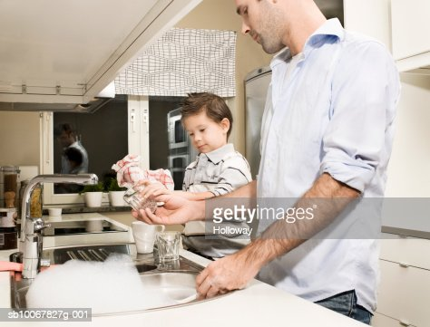 Father and son (4-5 years) washing dishes in kitchen, side view : Stock Photo