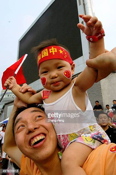 Father and son watch the Olympic Torch relay pass by The baby wears a red band with 'China go' on it