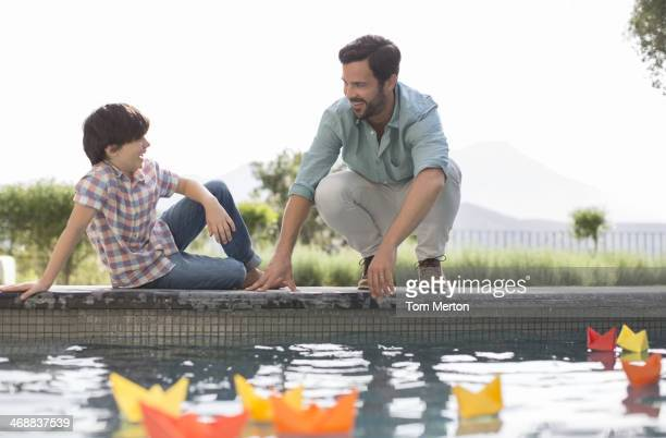 Vater und Sohn bei origami-Boote im Swimmingpool
