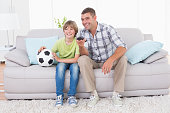 Happy father and son watching soccer match while sitting on sofa at home