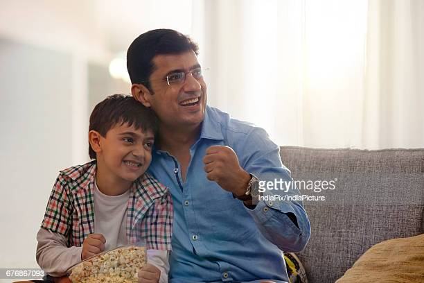 Father and son watching sports program in the television and eating popcorn