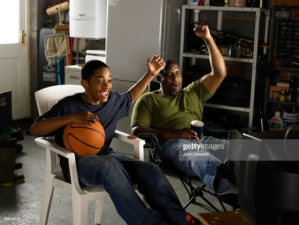 Father and Son watching TV and celebrating  : Stock Photo
