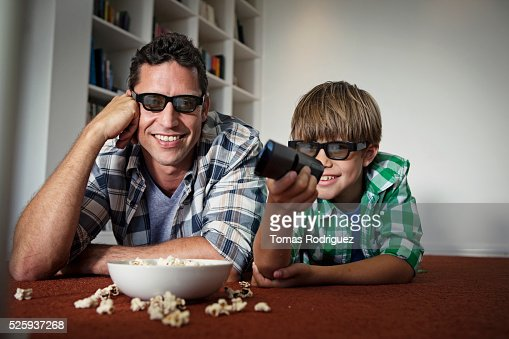 Father and son (6-7) watching tv on floor : Stockfoto