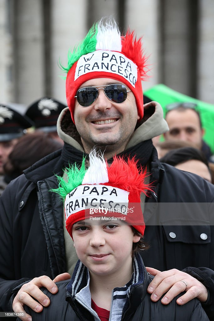 A father and son wear hats and wigs in support of Pope Francis before his first Angelus blessing on March 17, 2013 in Vatican City, Vatican. The Vatican is preparing for the inauguration of Pope Francis on March 19, 2013 in St Peter's Square.
