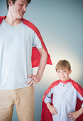 Father and son wearing superhero capes