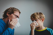 father and son wiping and blowing nose, family infection or allergy